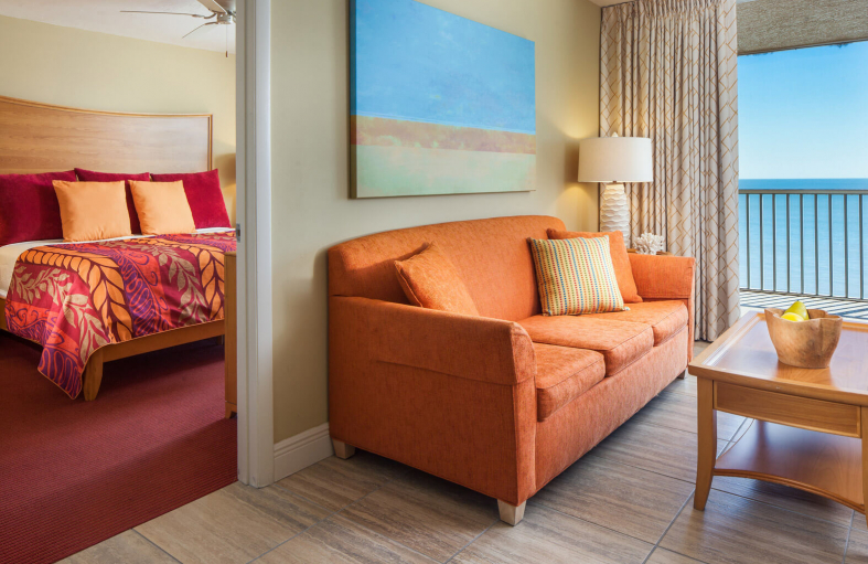 View of an orange couch in hotel living room with bedroom in the background