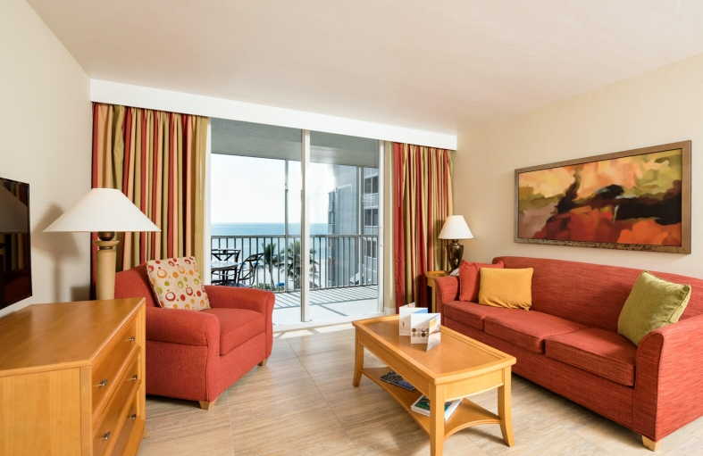 In room living space with red sofa, wooden coffee table, dresser with TV & balcony