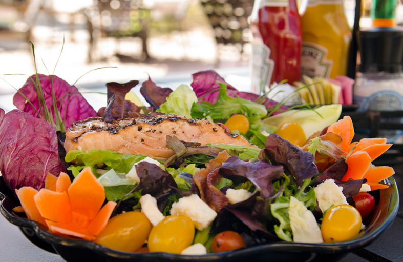 Colorful salad with salmon on table outside