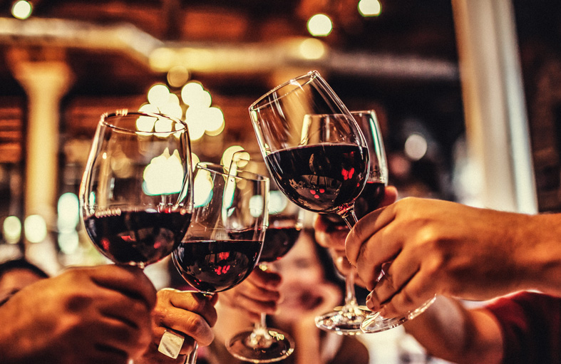 group of hands toasting with red wine