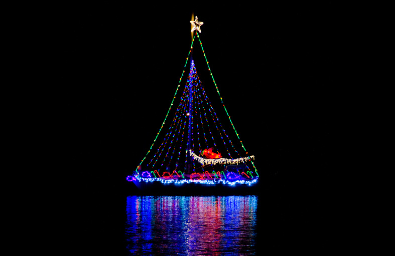 Sailboat decorated with Christmas lights on water