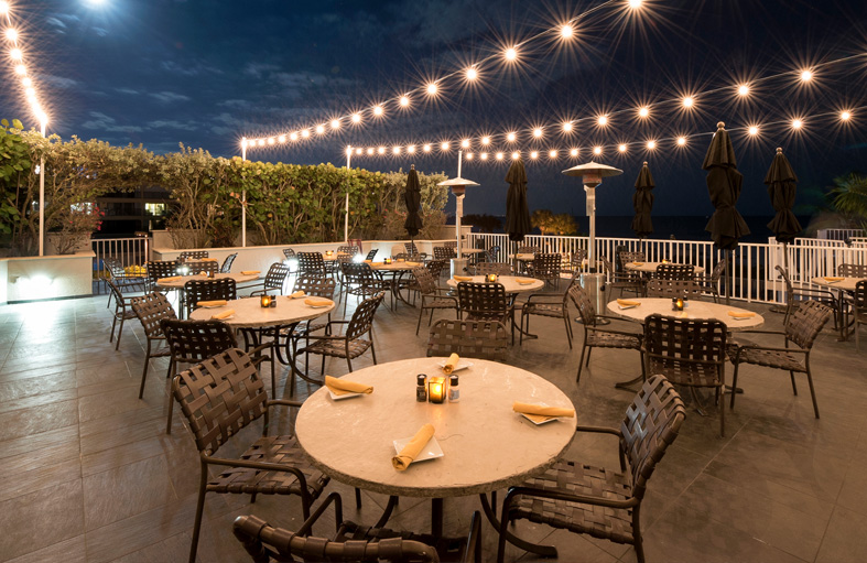 Balcony dining with metallic tables, chairs & decorative strung lightbulbs