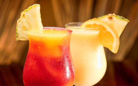 Close up shot of two colorful cocktails with slices of pineapple on the glasses