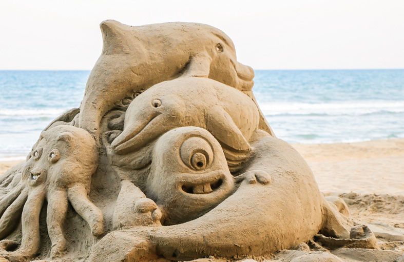 Elaborate sea creature sand sculpture with ocean in the back