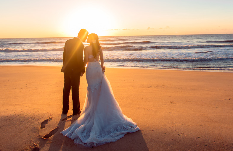 Wedding couple kissing on beach with sun setting in the back