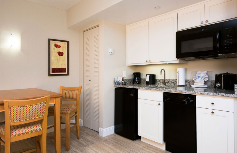 Kitchen with microwave, mini fridge, dishwasher, sink and a wooden dining table with chairs