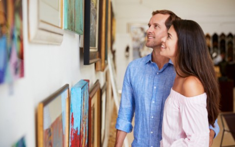 couple looking at paintings in art gallery