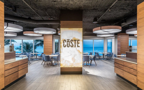 entryway of coste island cuisine with floor to ceiling windows looking out on the ocean