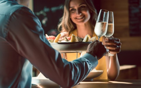 young couple toasting with champagne over dinner