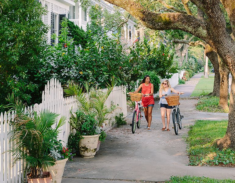 Two women walk alongside their bicycles on a sidewalk next surrounded by greenery and white picket fences
