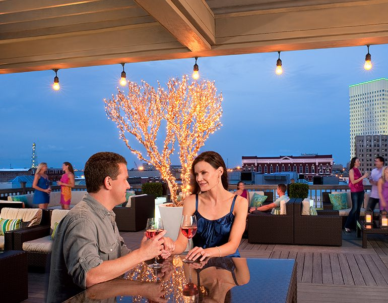 A couple sits together at a table drinking wine on a rooftop terrace