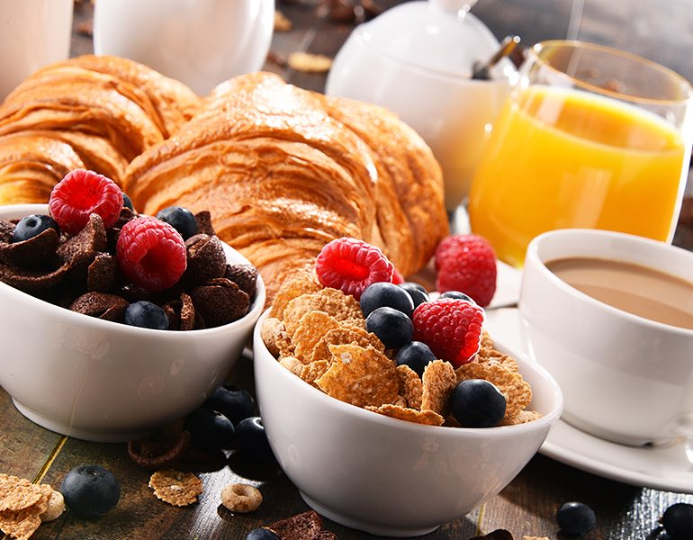 A table full of breakfast foods such as yogurt bowls, cereal, orange juice, coffee, and croissants