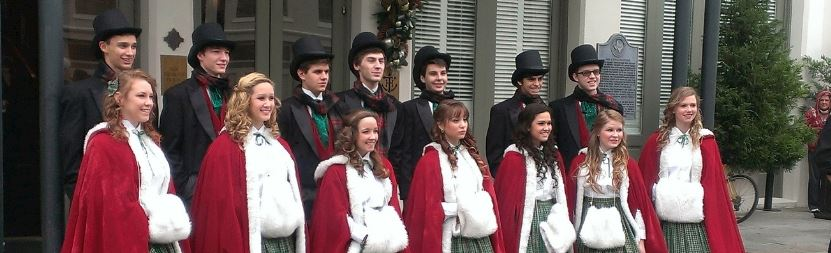 a men and women's choir in Christmas costumes singing outside a building