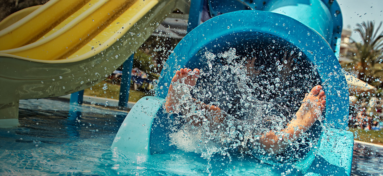 little kid coming down a waterslide at a waterpark
