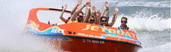a group of people with their hands in the air while on a jet boat ride in the water