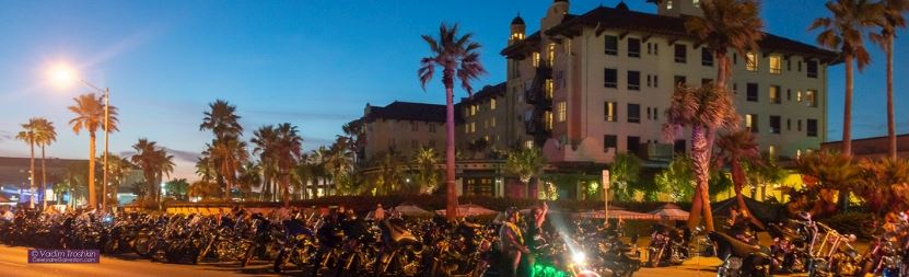 a long row of motorcycles lined up near hotel galvez at night