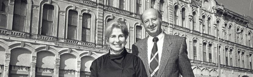 black and white image of a man and woman smiling outside a hotel