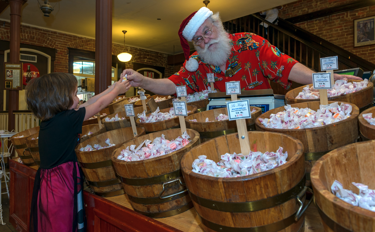 santa serving taffy to child
