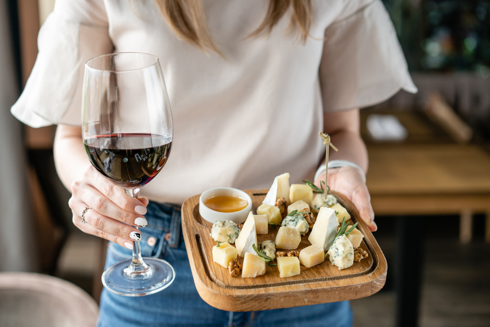 woman holding red wine and cheese plate