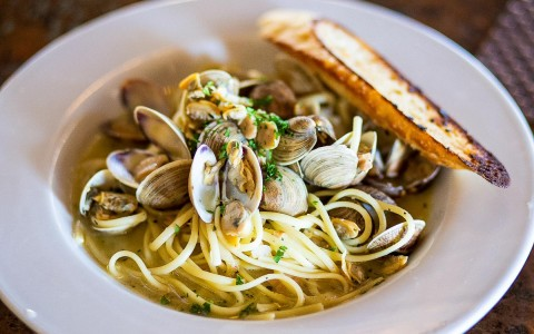 plate of spagghetti with clams and bread