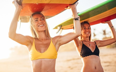 two women with surfboards on their head