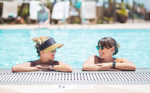 woman in sun hat and woman in sunglasses hanging out inside a pool