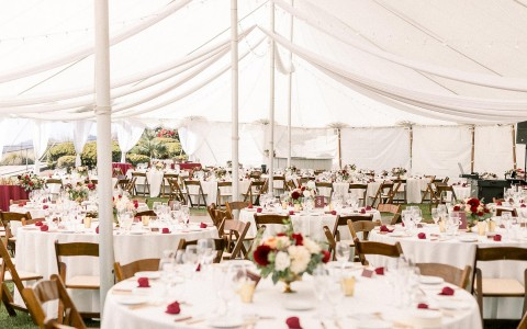 wedding tent with multiple round dining tables with rose decorations