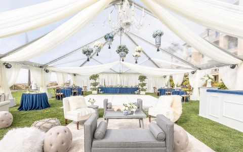 beautifully decorated tent with lace and chandeliers and blue reception tables
