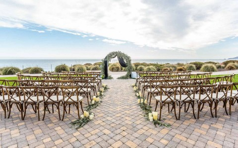 wedding altar outside with view of the ocean