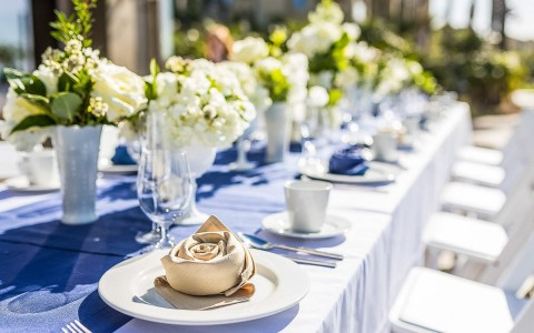 row of plates on a wedding reception table with white floral arrangements