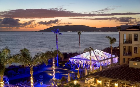 view of a lit up wedding reception tent by the water at sunset