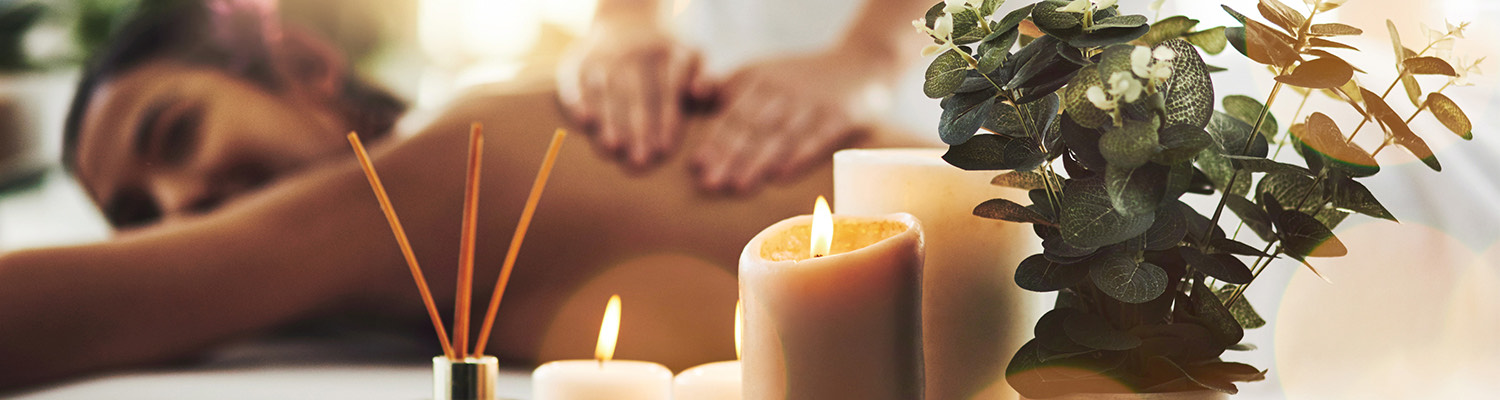 candles at a spa as a woman gets a massage