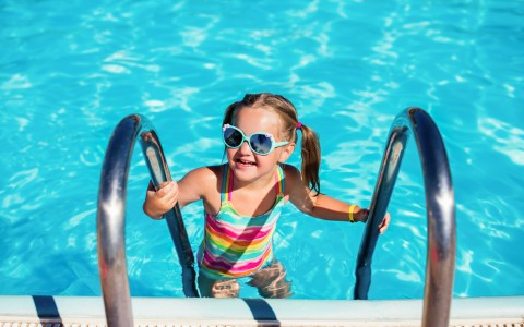 Little girl in the pool climbing up side ladder