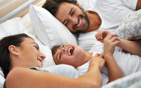 Parents and son playing in bed