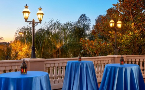reception tables set up on the terrace with blue table clothes and candle lantern decor