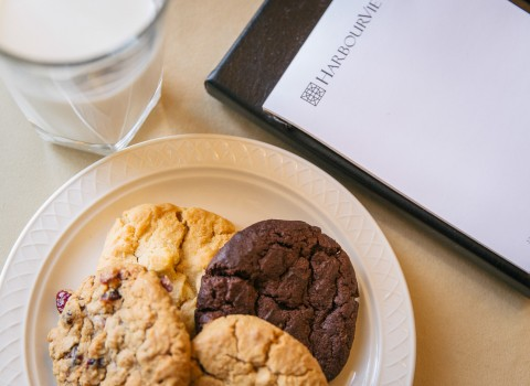 cookies on a plate with a glass of milk and a notepad
