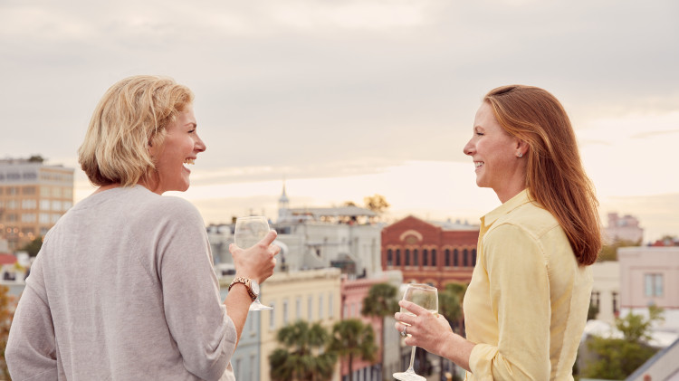 two women on a rooftop having wine