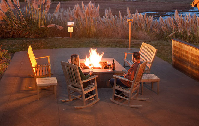 Couple sitting on rocking chairs around outdoor fire pit at night