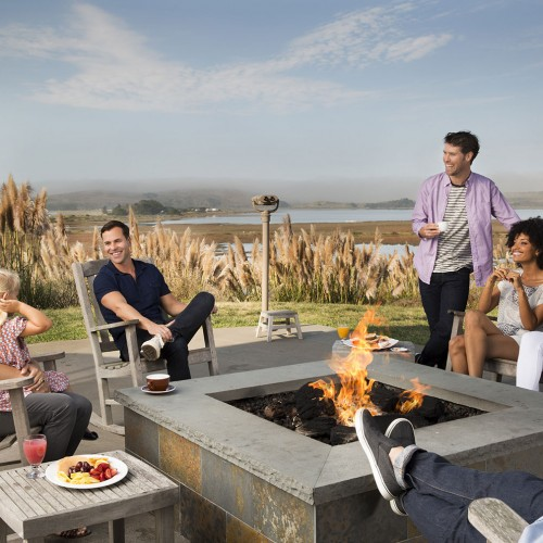 Group of friends laughing as they are gathered around outdoor fire pit