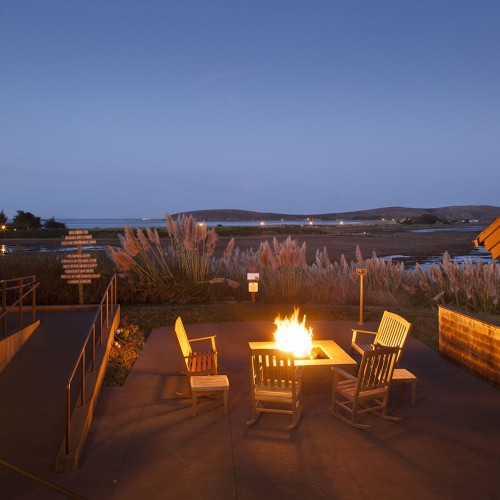 Outdoor fire pit lit up at night surrounded by rocking chairs