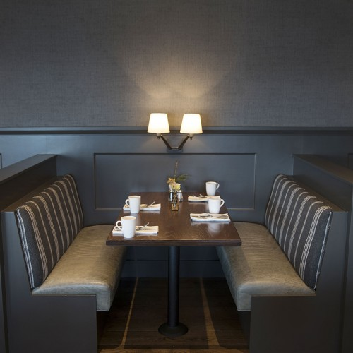 Dining booth with padded chairs, tea cups & small lamps