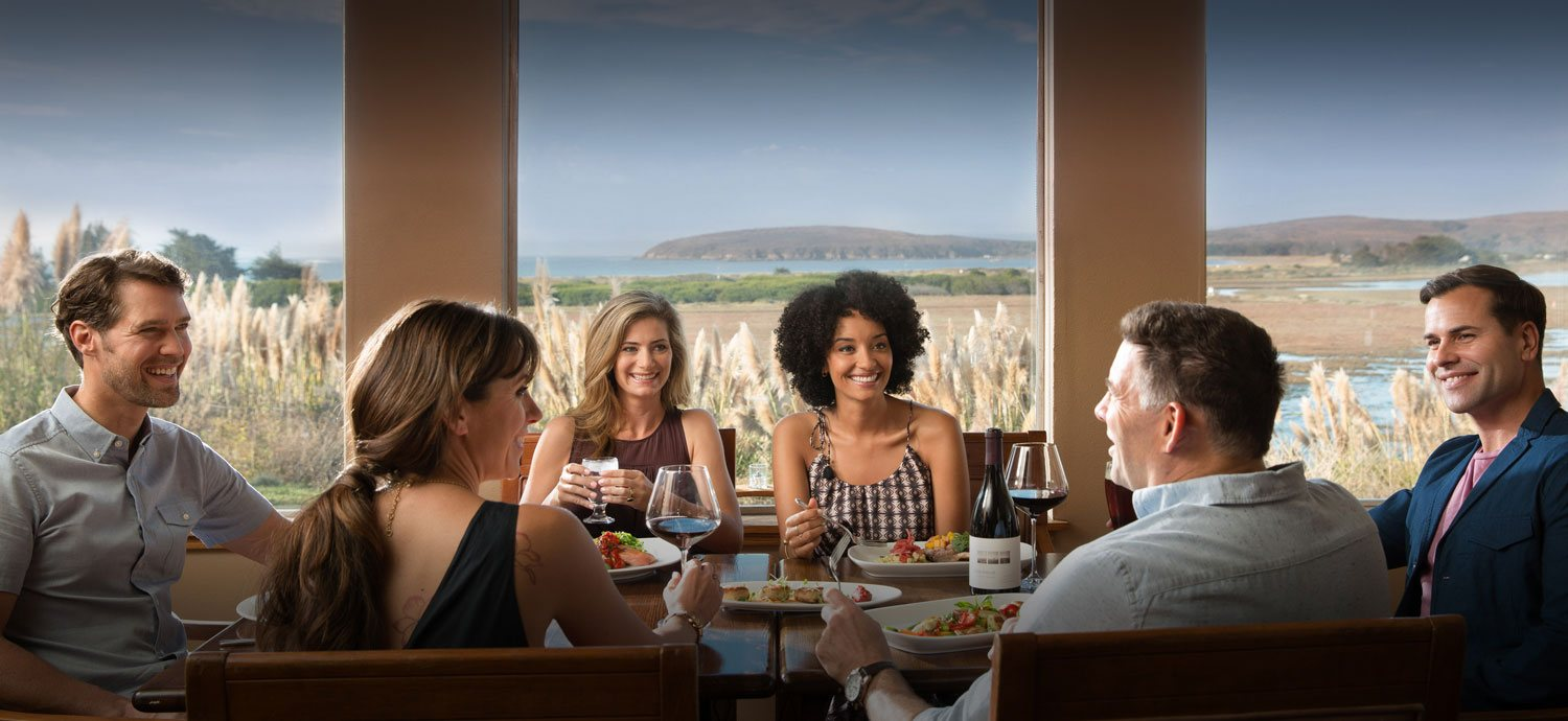 Group of friends dining on long wooden table with view of vast grassland & water