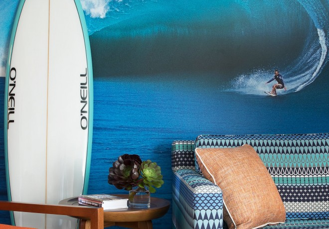 Lounge area with couch and propped surfboard