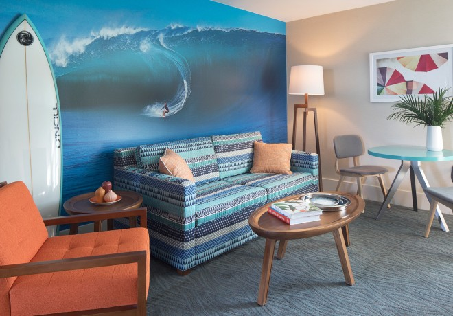 Lounge area with seating and tables in front of a mural of someone surfing