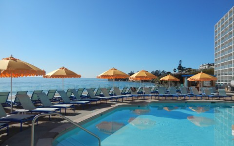 view of pool with yellow umbrellas and lounge chairs looking out to ocean
