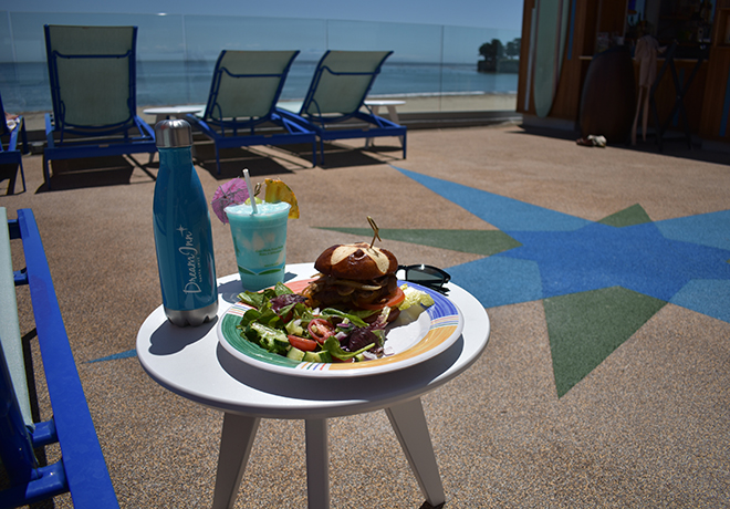 sandwich and salad on the pool deck with a blue frozen drink and a branded dream inn waterbottle