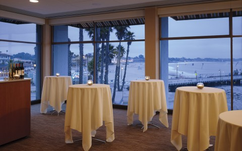 event room with cocktail tables, bar and floor to ceiling windows with ocean view