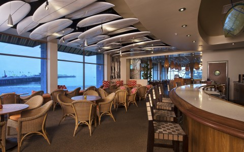 dining room and bar with oceanview and surfboards on ceiling