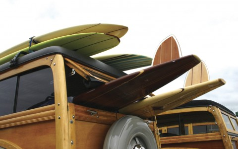 old jeep with surfboards on top and hanging out of the back