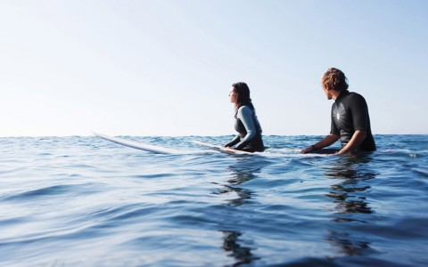 two surfers sitting on surfboards in very blue water